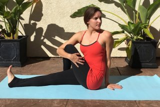 A young woman sitting in a seated twist yoga pose