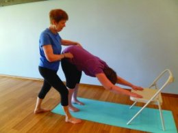 Margaret assisting a student in modified downward facing dog pose