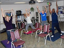 Patients and therapist performing standing yoga stretches.