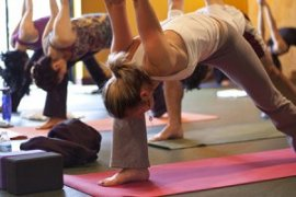 Photo: several people practicing yoga in a class