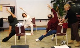 Two therapists lead and assist with stretching exercises while sitting.